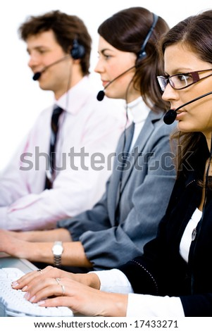 Customer service team working in headsets, woman in front. - stock photo