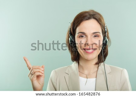 Customer service woman smiling and pointing with finger up. Copy space. - stock photo