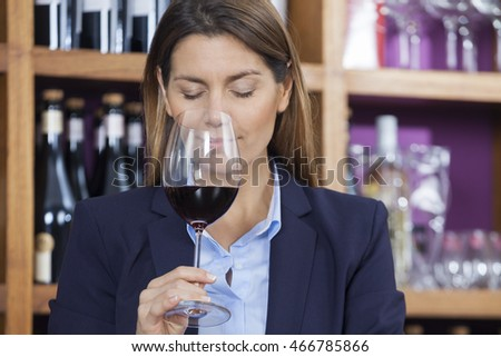 Customer Smelling Red Wine In Shop