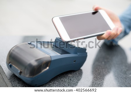 Customer using cellphone to pay - stock photo