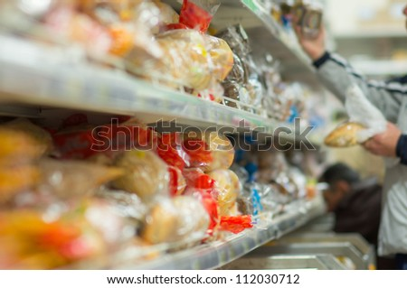 Customers select variety of bread on shelves in supermarket - stock photo