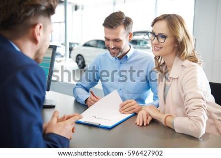 Customers signing contract at car dealer shop