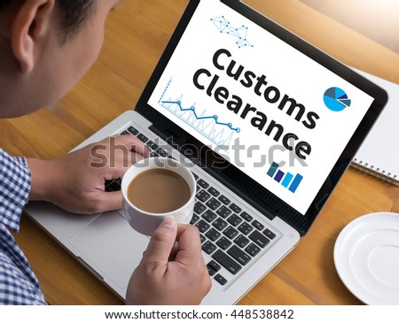 Customs Clearance Businessman at work. Close-up top view of man working on laptop while sitting at the wooden desk , coffee - stock photo