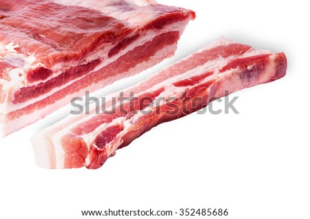 Cut a piece of bacon next to a large isolated on white background