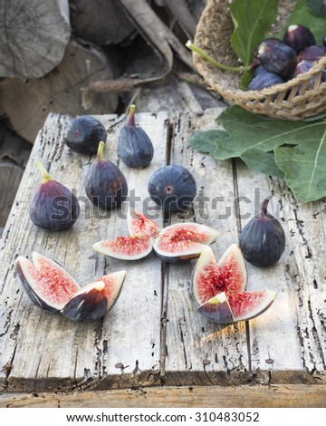 Cut and whole figs. Fresh figs and basket full of this fruit on wooden table - stock photo