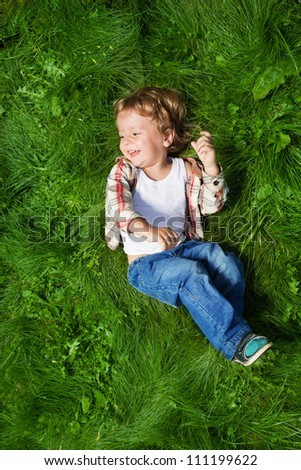 cut boy laying on the green grass and rolling - stock photo