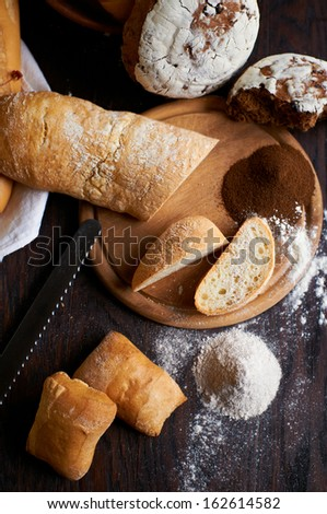 Cut ciabatta and rye bread on the cutting board with selective focus - stock photo