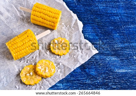 Cut corn on the cob with white crystals on paper - stock photo