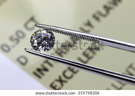 cut diamond held by tweezers above certificate - stock photo