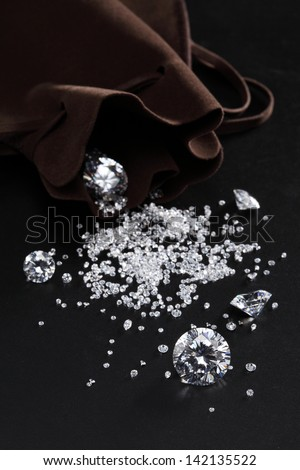 cut diamonds on shiny black surface close up. more diamonds out of focus in background  - stock photo