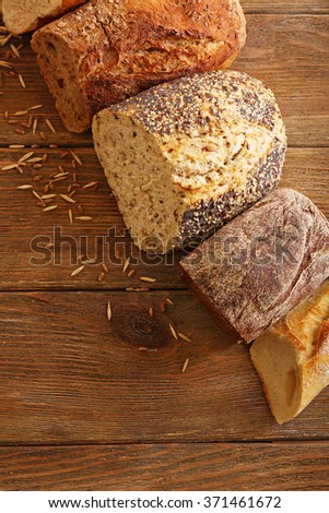 Cut fresh baked bread on the wooden background
