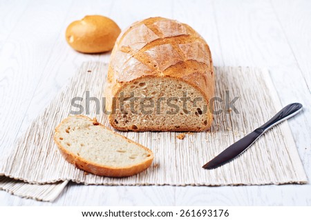Cut fresh bread on white table, selective focus - stock photo