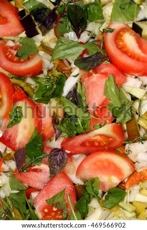 Cut fresh vegetable marrows with sliced tomatoes, onion and basil leaves prepared for stewing