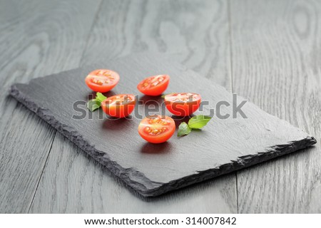 cut in half cherry tomatoes on slate board, shallow focus - stock photo