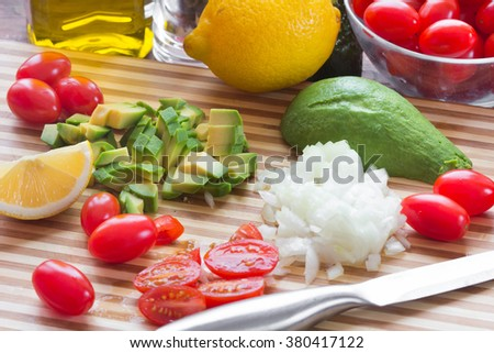 Cut ingredients (avocado, lemon, tomatoes, olive oil) for sauce guacamole