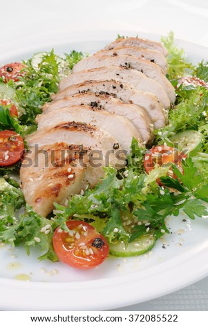 Cut into slices of grilled chicken breast with vegetable garnish - stock photo