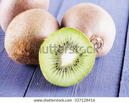 Cut kiwi over gray wooden table, horizontal image - stock photo