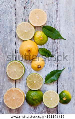 cut lime and lemon on a white wooden background - stock photo
