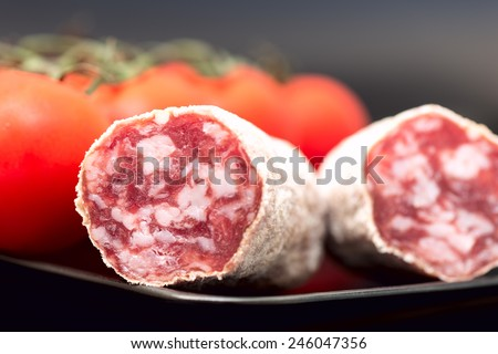 Cut of salami on plate with tomatoes - stock photo