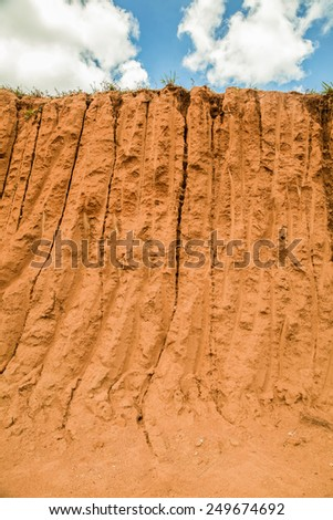 Cut of soil with different layers, grass and sky - stock photo