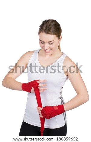 Cut out image of a young woman who is bandaging her hands for boxing with a red bandage
