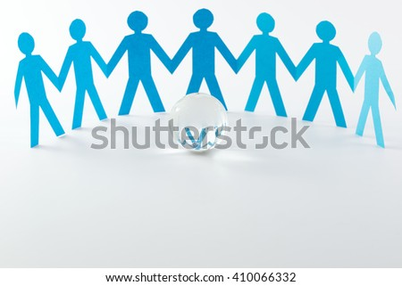 Cut out of blue paper people form in a semi circle in front of crystal globe - stock photo
