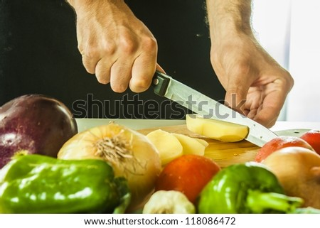 cut patatos with vegetables table - stock photo