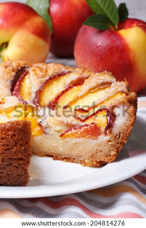 Cut peach pie on the background of fresh fruit on the table close-up. vertical