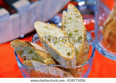 Cut pieces of white bread in a glass bowl on a red background. - stock photo