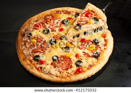 cut pizza on a dark background with ham, mushrooms, olives, cheese and sweet pepper top view - stock photo