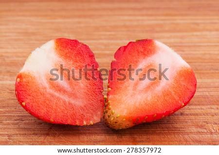 cut ripe strawberry lies on a chopping board - stock photo