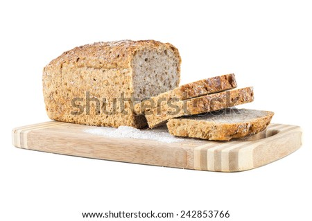 Cut wholemeal bread on a chopping board isolated on white background  - stock photo