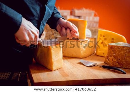 Cut with a knife piece of cheese on a dark table.