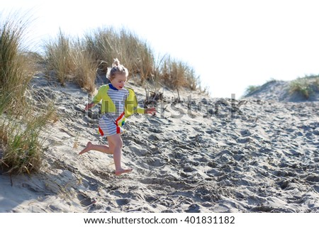 Cute active child wearing colorful dress playing on wide sandy beach jumping in dunes. Happy little girl enjoying summer holidays on a sunny day. Family with young kids on vacation at North Sea coast. - stock photo