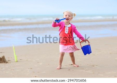 Cute active child wearing pink dress playing, singing and dancing on sandy beach. Happy little girl enjoying summer holidays on a sunny day. Family with young kids on vacation at the North Sea coast. - stock photo