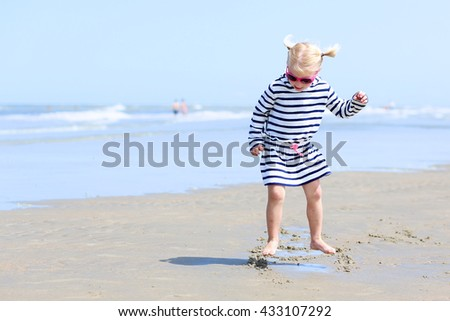 Cute active child wearing pink sunglasses playing and running on wide sandy beach. Happy little girl enjoying summer holidays on a sunny day. Family with young kids on vacation at the North Sea coast - stock photo
