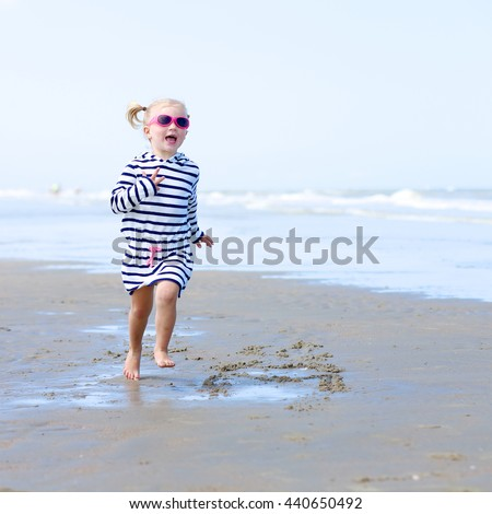Cute active child wearing pink sunglasses playing and running on wide sandy beach. Happy little girl enjoying summer holidays on a sunny day. Family with young kids on vacation at the North Sea coast.