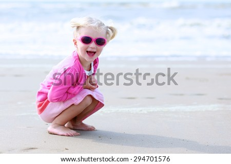 Cute active child wearing pink sunglasses playing on wide sandy beach. Happy little girl enjoying summer holidays on a sunny day. Family with young kids on vacation at the North Sea coast. - stock photo