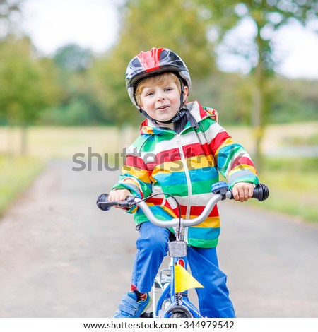 Cute active little boy riding on bike on warm summer day. Countryside. Child in helmet. Active leisure and sports for kids. - stock photo
