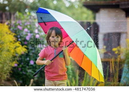 Cute adorable child, boy, playing with colorful umbrella under sprinkling water in his backyard