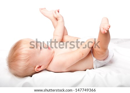 Cute adorable infant baby laying on back with feet up in the air wearing diapers, on white. - stock photo