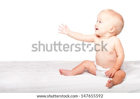 Cute adorable infant baby reaching out with hand asking for something while sitting, on white. - stock photo