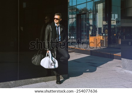 Cute adult man standing near black wall and looking aside outdoors - stock photo