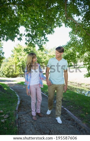 Cute affectionate couple walking hand in hand in the park on a sunny day - stock photo