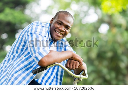 cute african american man on a bicycle outdoors - stock photo