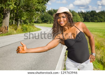 Cute African American woman hitchhiking - stock photo