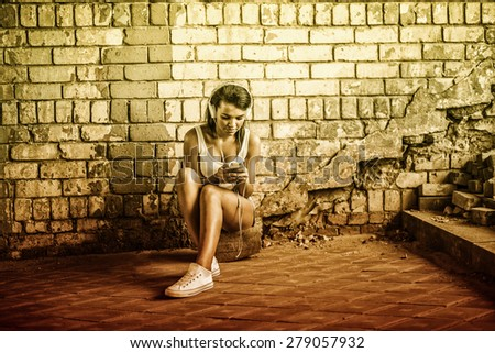 Cute african black girl sit near cracked grunge yellow brick wall with big white headphones Female hold in head mobile phone Portrait of young adult attractive afro american woman listening music - stock photo