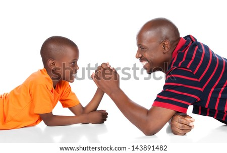 Cute african boy wearing a bright orange t-shirt and dark denim jeans is playing arm wrestle with his father. - stock photo