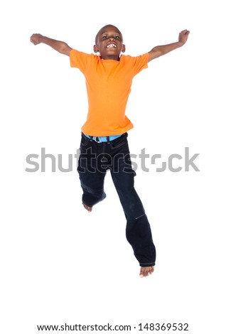 Cute african boy wearing a bright orange t-shirt and dark denim jeans. The boy is jumping and smiling. - stock photo