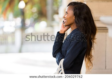 cute african woman talking on mobile phone outdoors